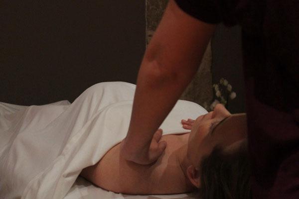 Séance de massage d'une femme enceinte allongée sur le dos